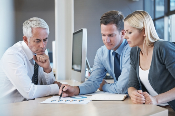 Shot of a group of business people going over statistics
