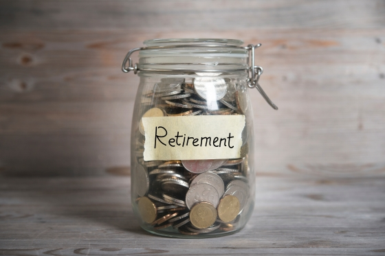 Coins in glass jar with retirement label, financial concept. Vintage wooden background with dramatic light.