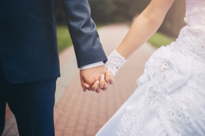 Close up of bride and groom holding hands.
